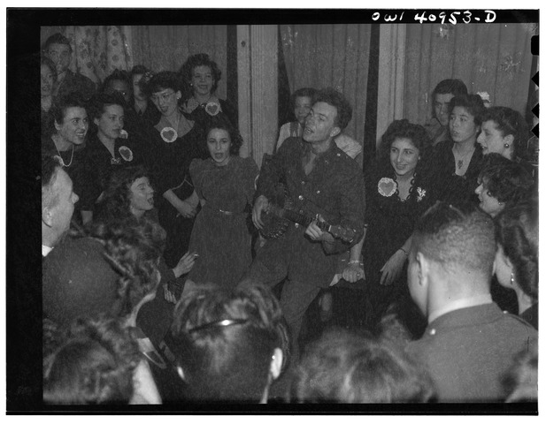 Pete in Army uniform surrounded by people singing, 1941