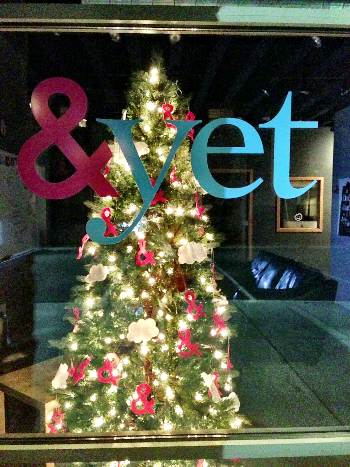 a christmas tree decorated with ampersands behind the &yet logo